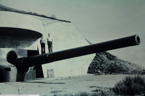 Men stand on anti-aircraft battery